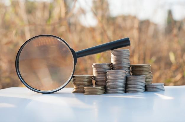 Lupe des einsparungsgeldes mit dem münzenstapel, der auf natursonnenuntergang wächst