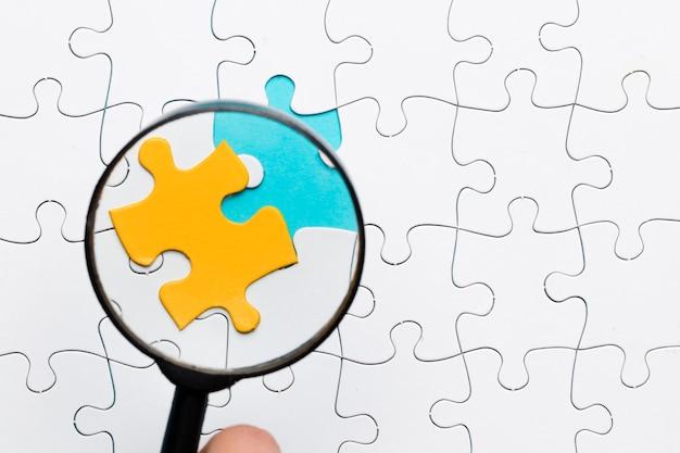 Lupe, die auf gelbes puzzlespielstück über weißem puzzlespielstückhintergrund sich konzentriert