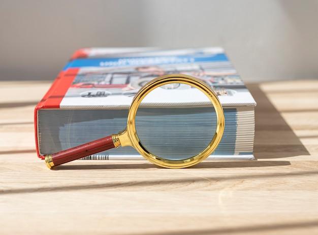 Lupe in der nähe eines dicken fachbuchs für das bildungskonzept wissenschaftlicher kenntnisse und studien