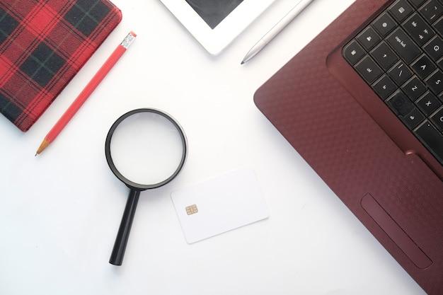 Lupe, kreditkarte und laptop auf weißem hintergrund.