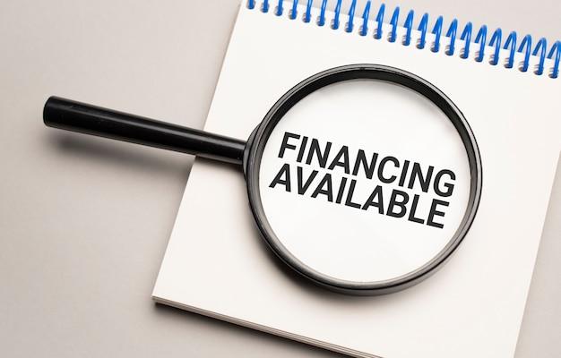 Lupe mit dem wort finanzierung auf diagrammhintergrund verfügbar