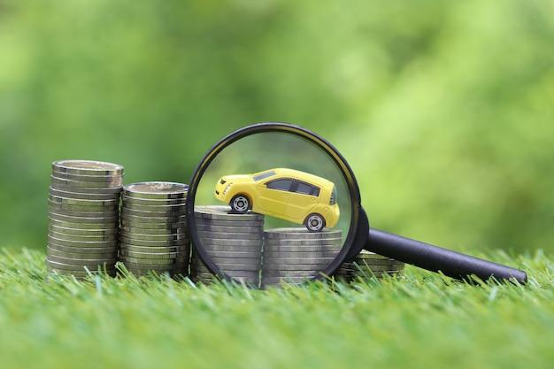 Lupe mit gelbem miniaturautomodell auf wachsendem stapel von geldmünzen auf naturgrünfläche