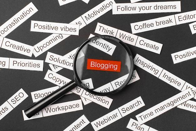Lupe über der roten inschrift blogging aus papier geschnitten. umgeben von anderen inschriften auf einem dunklen hintergrund. word-cloud-konzept.