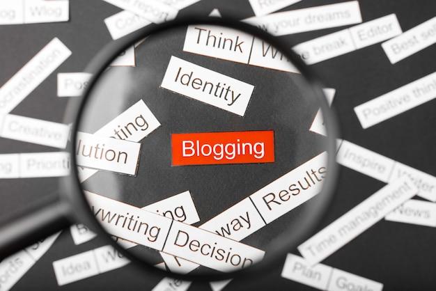 Lupe über der roten inschrift blogging aus papier geschnitten. umgeben von anderen inschriften auf einem dunklen. wortwolke.