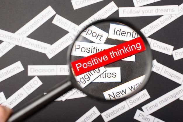 Lupe über der roten inschrift positives denken aus papier ausgeschnitten. umgeben von anderen inschriften auf einem dunklen hintergrund. word-cloud-konzept.