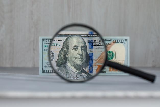 Lupe über dollarbanknote auf grauem und hölzernem tisch