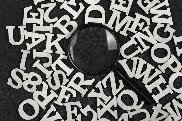 Lupe umgeben von buchstaben des englischen alphabets auf schwarzem hintergrund. suchwortkonzept