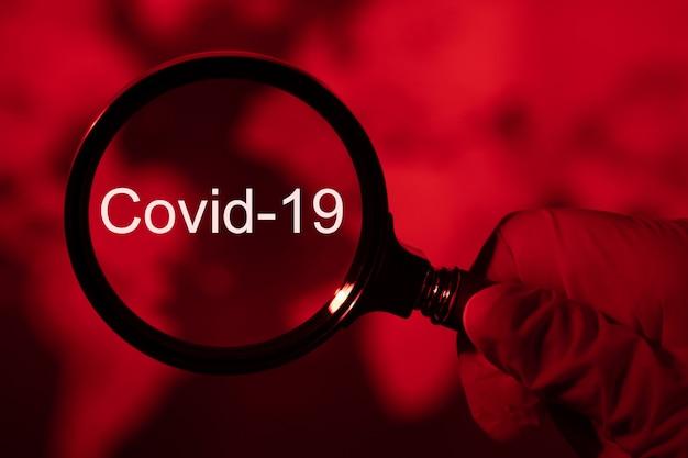 Lupe und coronavirus, rot getönte weltkarte, konzept covid-19
