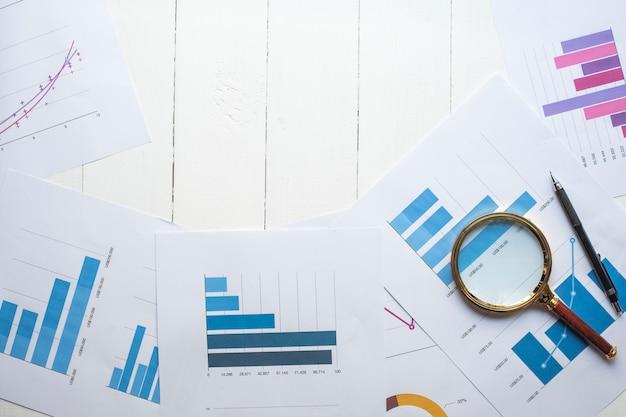Lupe und dokumente mit den analytikdaten, die auf tabelle, selektiver fokus liegen