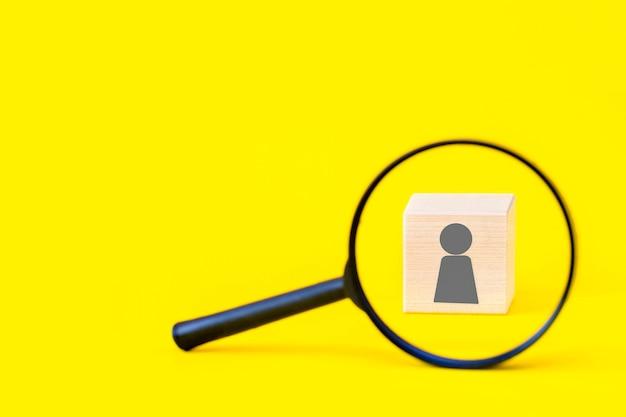 Lupe und ein holzwürfel mit einer menschlichen ikone auf gelb mit kopienraum.