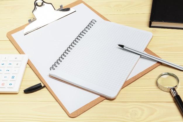 Lupe und notizbuch auf holztisch