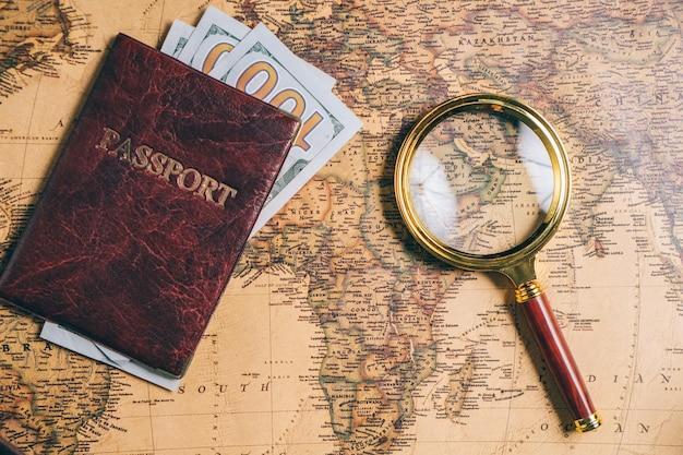 Lupe und reisepass mit geld auf einer vintage-weltkarte. von oben betrachten.