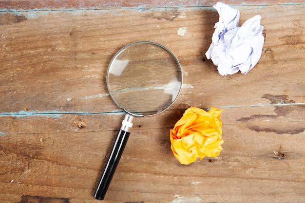 Lupe und zerknitterte papiere auf einem holztisch. konzept suche nach einer idee