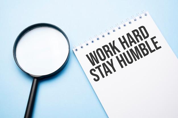 Lupenlupe mit zeichen work hard stay humble blauer tisch.