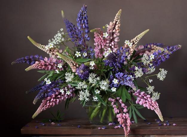 Lupinen in einer transparenten vase. stilleben mit einem blumenstrauß aus im garten gepflegten blumen.