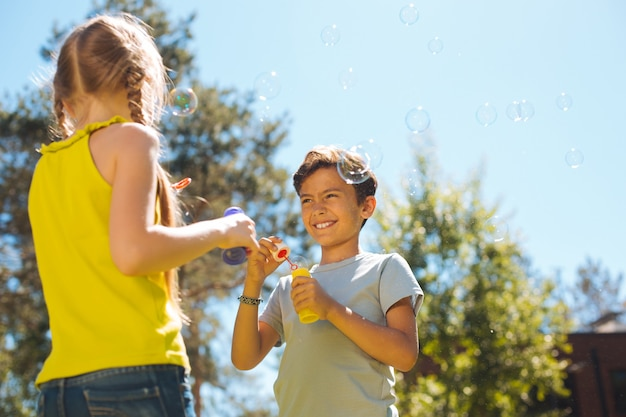 Lustig. üppige entzückende kinder, die spaß haben und seifenblasen blasen