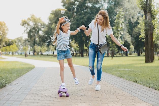 Lustig und kostenlos. lächelnde ansprechende vorschulmädchen fühlen sich lustig und frei, während sie ihr skateboard benutzen