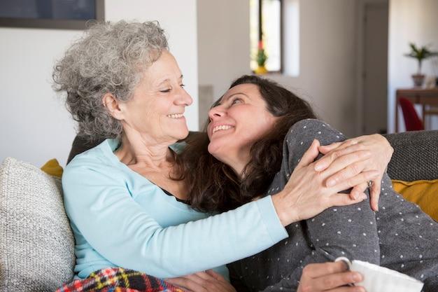 Lustige ältere mutter und ihre tochter, die sich zu hause auf sofa entspannt
