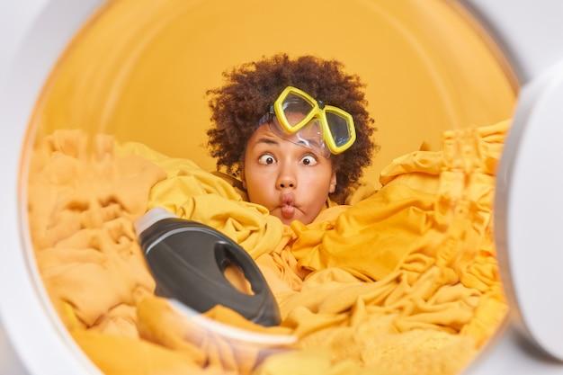 Lustige afro-amerikanerin macht fischlippen trägt schnorchelmaske, kreuzt die augen in einem haufen wäsche mit waschmittelflaschenladungen waschmaschinenposen gegen gelbe wand