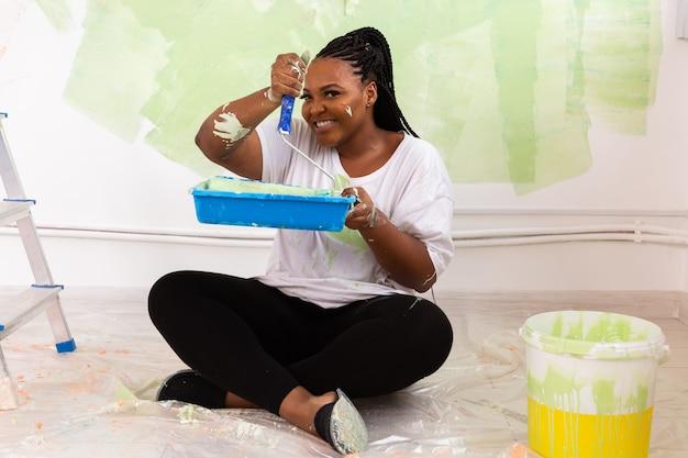 Lustige afroamerikanische frau, die eine wohnung malt. renovierungs-, reparatur- und renovierungskonzept.