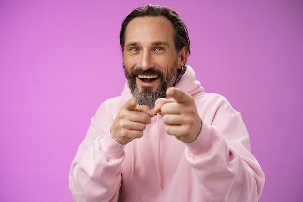 Lustige amüsierte sorglose glückliche erwachsene gutaussehende mann streich freund narr herum zeigen kamera zeigefinger gruß auswahl wählen sie lachen freudig mit fu, stehend lila hintergrund freude.
