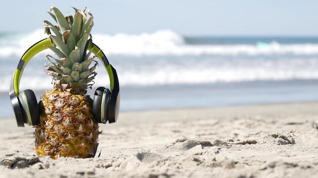 Lustige ananas in kopfhörern, sandstrand am meer, blaue meerwasserwellen, kalifornische pazifikküste, usa. exotische frucht des tropischen sommers, die ferien und musik im paradies genießt. ananas beim sonnenbaden am ufer