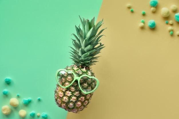 Lustige ananas mit sonnenbrille, flach auf gespaltener neo-minze und khaki-papier