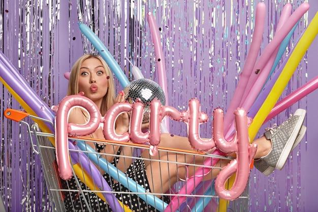 Lustige angenehm aussehende blonde frau im einkaufswagen mit langen modellierballons und discokugel, trägt kleid und sportschuhe, schaut in die kamera hat gefaltete lippen, hat spaß auf lauten party mit kollegen