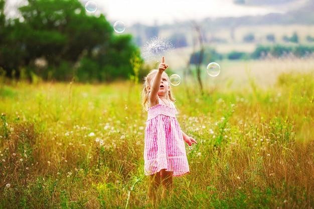 Lustige anziehende seifenblasen des kleinen mädchens im sommer auf natur. happy kindheit konzept