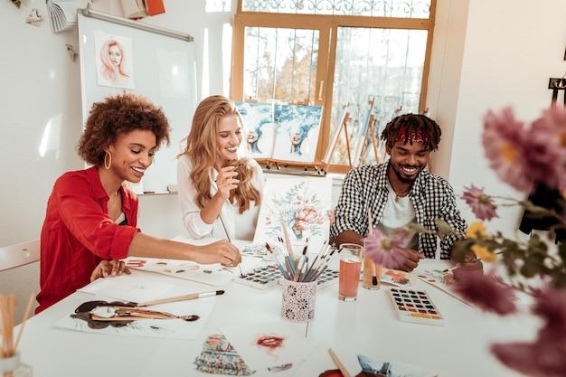 Lustige arbeit. drei kreative talentierte künstler lachen, während sie sich lustig fühlen, wenn sie zusammenarbeiten