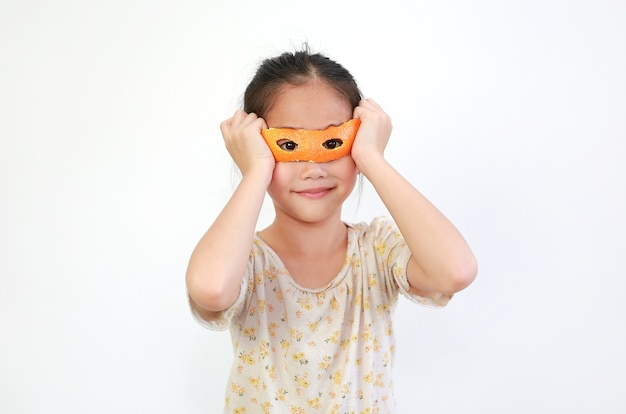 Lustige asiatische kleine mädchen spielen tragen brille aus orangenschale