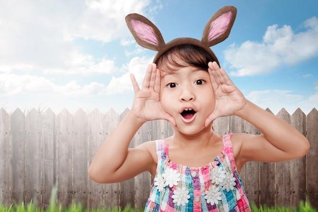 Lustige asiatische tragende häschenohren des kleinen kindes, die ostern-feiertag feiern