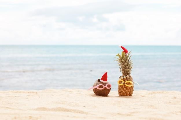 Lustige attraktive ananas und kokosnuss in stilvoller sonnenbrille auf dem sand gegen türkisfarbenes meer. weihnachtsmützen tragen. Premium Fotos