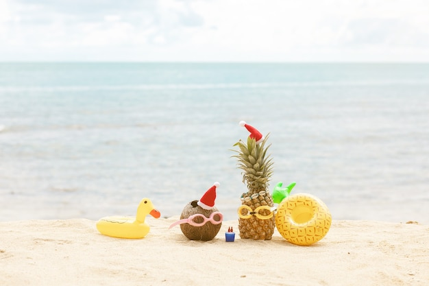 Lustige attraktive ananas und kokosnuss in stilvoller sonnenbrille auf dem sand gegen türkisfarbenes meer. weihnachtsmützen tragen.