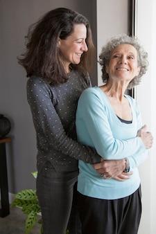 Lustige aufgeregte ältere frau umarmt von der tochter, die sich zurück dreht