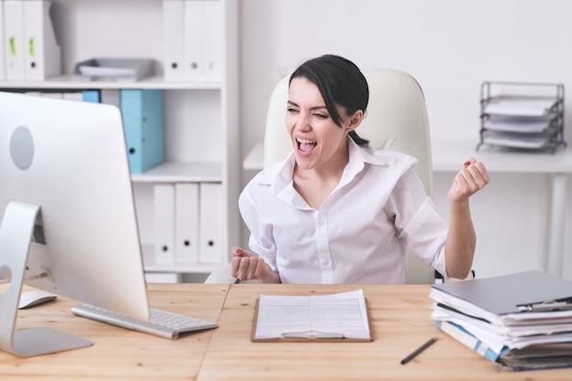 Lustige aufgeregte junge managerin in weißer bluse, die auf computermonitor schaut und ja-geste macht, während sie zart gewinnt
