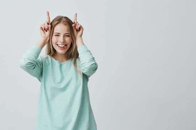 Lustige blonde frau lächelt breit und hält die finger über dem kopf. hörnergeste