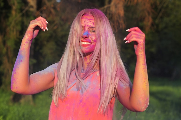 Lustige blonde frau mit flatternden haaren posiert mit bunter farbe beim holi-festival