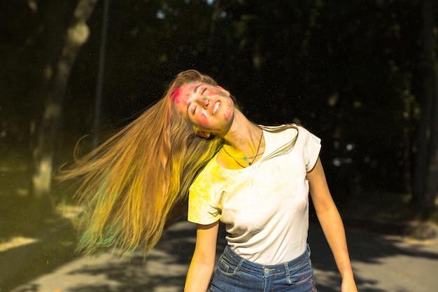 Lustige blonde frau mit wind im haar und leuchtenden farben, die um sie herum explodieren