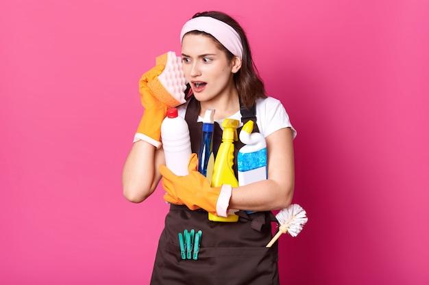 Lustige charmante junge kaukasische hausfrau, die lässiges t-shirt und schürze, orangefarbene gummihandschuhe trägt, schwämme im gesicht hält, stellt sich vor, dass telefon ist, hat spaß bei der hausarbeit. hygienekonzept.
