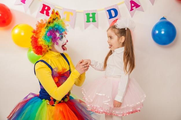 Lustige clowns im urlaub zeigen ihre guten gefühle mit einem mädchen