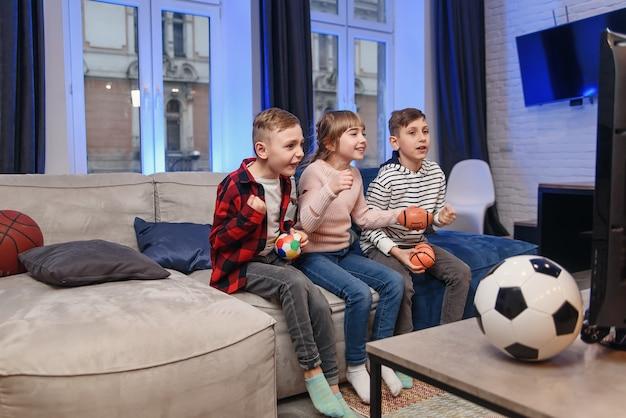 Lustige drei kinderfreunde sitzen zu hause auf der couch und genießen fußballspiel