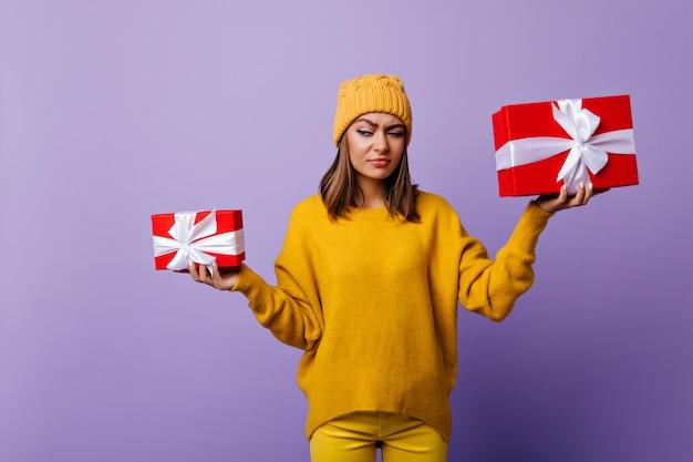 Lustige dunkelhaarige dame im stilvollen hut, der geschenkboxen hält. porträt der ansprechenden brünetten frau im gelben pullover, der vor weihnachten aufwirft.