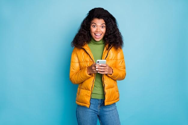 Lustige dunkle haut dame offenen mund halten telefon hände genießen neue blog-anhänger tragen gelbe frühlingsmantel jeans pullover isoliert blaue farbe wand