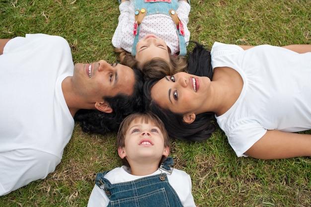 Lustige eltern und ihre kinder, die auf dem gras liegen