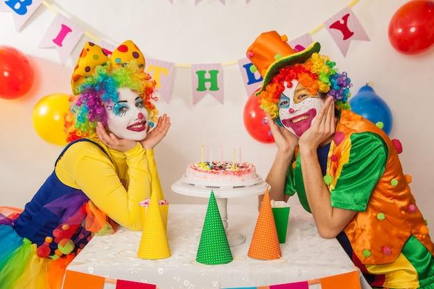 Lustige emotionale clowns auf der party können den kuchen nicht teilen