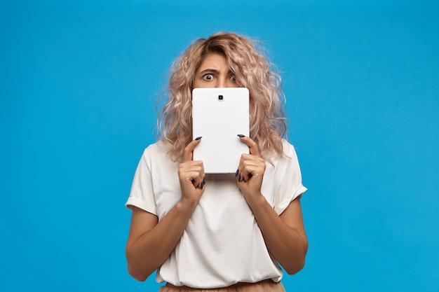 Lustige emotionale junge frau in der trendigen runden hipsterbrille, die gesicht mit generischem digitalem tablett bedeckt, mit großen abgehörten augen