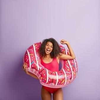Lustige energische junge frau mit dem lockigen haar, das mit schwimmendem pool aufwirft