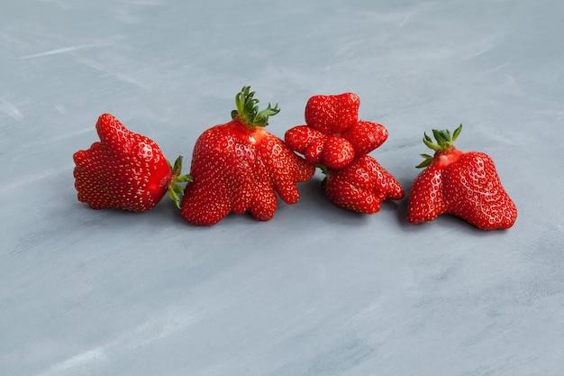 Lustige erdbeerbeeren. trendiges essen. hässliches obst und gemüse essen.