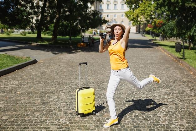 Lustige erstaunte reisende touristenfrau mit hut mit koffer, die sich an den kopf klammert, halten retro-vintage-fotokamera, die in der stadt im freien springt. mädchen, das am wochenende ins ausland reist. tourismus reise lebensstil.